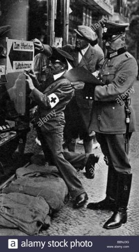 evenements-seconde-guerre-mondiale-seconde-guerre-mondiale-guerre-aerienne-allemagne-policier-et-aides-de-la-croix-rouge-allemande-joignant-un-panneau-de-direction-indiquant-le-refuge-public-de-raid-aerien-berlin-fin-aout-1939-bbnj3g.jpg